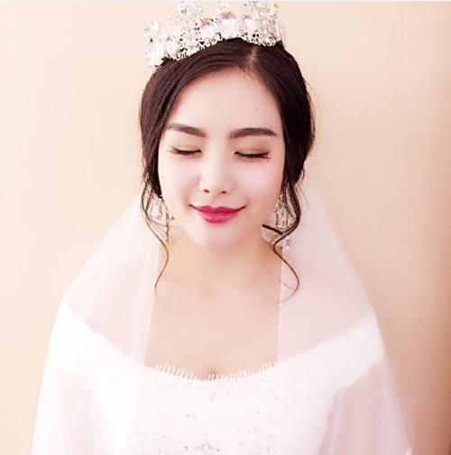 圆脸的新娘选择的是无刘海的辫子风格的盘发发型,头发的风格是很