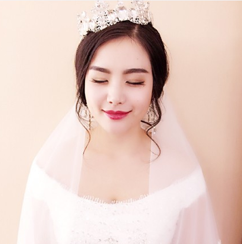 圆脸的新娘选择的是无刘海的辫子风格的盘发发型,头发的风格是很独特图片